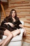 Mujer morena atractiva joven hermosa que lleva un diseño elegante y un abrigo de pieles de moda, pierna fina larga del vestido co imagen de archivo libre de regalías