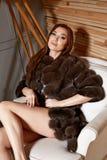 Mujer morena atractiva joven hermosa que lleva un diseño elegante y un abrigo de pieles de moda, pierna fina larga del vestido co foto de archivo
