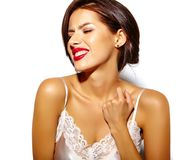 Mujer morena atractiva linda feliz hermosa con los labios rojos en ropa interior de los pijamas en el fondo blanco imagenes de archivo