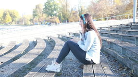 Mujer morena atractiva que escucha la música con los auriculares en el parque metrajes