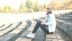 Mujer morena atractiva que escucha la música con los auriculares en el parque almacen de video