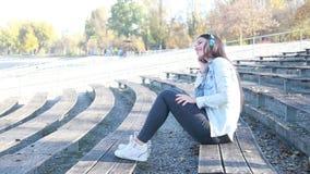 Mujer morena atractiva que escucha la música con los auriculares en el parque almacen de metraje de vídeo