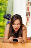 Mujer morena bastante joven que miente hacia abajo sujetando la prueba casera del embarazo en el frente, pareciendo subrayado, es Fotografía de archivo libre de regalías