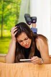 Mujer morena bastante joven que miente hacia abajo sujetando la prueba casera del embarazo en el frente, pareciendo subrayado, es Imagen de archivo libre de regalías