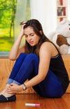 Mujer morena bastante joven que se sienta en piso con la prueba del hogar del embarazo que miente en el frente, mirando desespera Foto de archivo libre de regalías