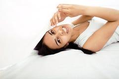 Mujer morena bastante linda en cama debajo de las hojas Imagenes de archivo