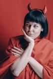 Mujer morena bonita con los cuernos del diablo rojo Foto de archivo libre de regalías