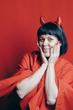 Mujer morena bonita con los cuernos del diablo rojo Fotos de archivo