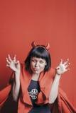 Mujer morena bonita con los cuernos del diablo rojo Fotos de archivo libres de regalías