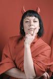Mujer morena bonita con los cuernos del diablo rojo Foto de archivo