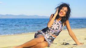 Mujer morena bonita en la playa y entretenida hablando en el teléfono celular metrajes