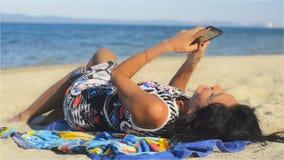 Mujer morena bonita en la playa y entretenida hablando en el teléfono celular almacen de metraje de vídeo