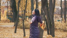 Mujer morena bonita joven feliz que hace girar con las hojas de otoño en el parque metrajes