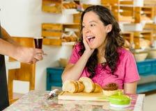 Mujer morena bonita que se sienta por la tabla dentro de la panadería, recibiendo el café express tirado de camarero y sonriendo  imagen de archivo libre de regalías