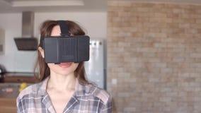 Mujer morena bonita que usa sus auriculares del teléfono móvil VR en casa Vidrios asequibles de la realidad virtual en la acción  almacen de video
