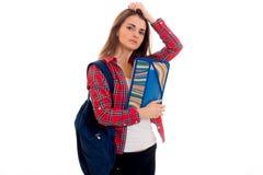 Mujer morena cansada joven del estudiante con la mochila azul en su hombro y carpeta para los cuadernos en las manos que miran Imágenes de archivo libres de regalías