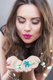 Mujer morena caucásica feliz que sostiene confeti del Año Nuevo Fotos de archivo libres de regalías