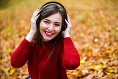 Mujer morena caucásica joven con los auriculares al aire libre en autum Fotografía de archivo libre de regalías