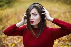 Mujer morena caucásica joven con los auriculares al aire libre en autum Fotografía de archivo
