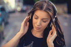 Mujer morena caucásica joven con los auriculares al aire libre en día de verano soleado Imágenes de archivo libres de regalías