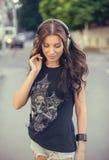 Mujer morena caucásica joven con los auriculares al aire libre en día de verano soleado Imagen de archivo libre de regalías