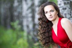 Mujer morena caucásica joven hermosa en vestido rojo al aire libre Imágenes de archivo libres de regalías
