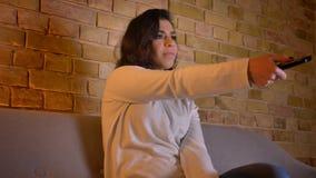 Mujer morena caucásica que se sienta en el sofá y que elige usar del programa teledirigido en atmósfera casera acogedora almacen de video