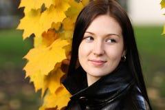Mujer morena con la hoja de oro del otoño Imagenes de archivo