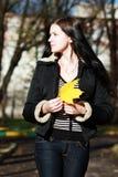 Mujer morena con la hoja de oro del otoño Imagen de archivo libre de regalías