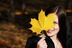 Mujer morena con la hoja de oro del otoño Fotografía de archivo libre de regalías