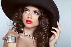 Mujer morena con los labios rojos, pelo ondulado, joyería de la belleza de la moda Foto de archivo libre de regalías