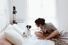 Mujer morena con su perrito dulce en dormitorio fotos de archivo libres de regalías
