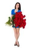 Mujer morena con un ramo grande de rosas rojas Imágenes de archivo libres de regalías