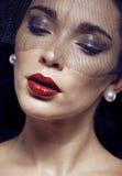 Mujer morena de la belleza debajo del velo negro con cierre rojo de la manicura para arriba, afligiéndose a la viuda, maquillaje  Fotos de archivo