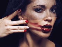 Mujer morena de la belleza debajo del velo negro con rojo Imagen de archivo