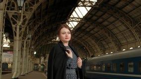 Mujer morena de mediana edad atractiva en una capa negra en el ferrocarril almacen de metraje de vídeo