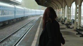 Mujer morena de mediana edad atractiva en una capa negra en el ferrocarril ?l el llover del ` s Primer de piernas que caminan ade metrajes