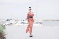 Mujer morena de moda joven que lleva el vestido largo en las gafas de sol que presentan cerca del mar, embarcadero con los yates Imagen de archivo libre de regalías