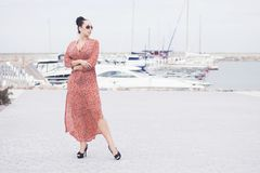 Mujer morena de moda joven que lleva el vestido largo en las gafas de sol que presentan cerca del mar, embarcadero con los yates Fotos de archivo