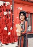 Mujer morena de pelo largo joven en un vestido y un sombrero brillantes contra una pared roja foto de archivo libre de regalías