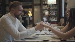 Mujer morena del encanto y un hombre rubio barbudo hermoso que se sienta en la tabla delante de uno a El decir del hombre almacen de video