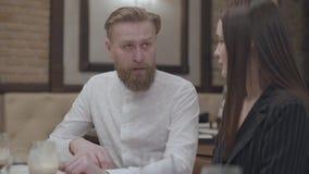 Mujer morena del encanto y un hombre rubio barbudo hermoso que se sienta en la tabla El hombre que cuenta una historia a su novia almacen de metraje de vídeo