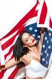 Mujer morena del patriota atractivo que sostiene la bandera de los E.E.U.U. imagen de archivo libre de regalías