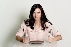 Mujer morena descontenta que espera una comida en una placa vacía Imagenes de archivo