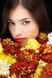 Mujer morena detrás de las flores Foto de archivo libre de regalías