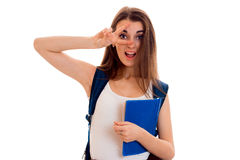 Mujer morena divertida joven del estudiante con la mochila azul en su hombro y carpeta para los cuadernos en las manos que miran Fotos de archivo