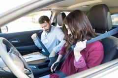 Mujer morena e instructor Wearing Car Seatbelts fotos de archivo libres de regalías