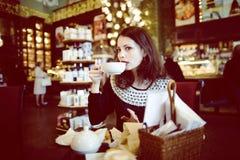 Mujer morena elegante joven en el café de consumición del café, interior de lujo Fotos de archivo