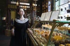 Mujer morena elegante joven en el café de consumición del café, interior de lujo Imagen de archivo libre de regalías