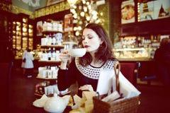 Mujer morena elegante joven en el café de consumición del café, interior de lujo Imágenes de archivo libres de regalías
